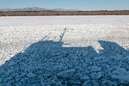 The United States Coast Guard cutter Sturgeon Bay casts a shadow as it breaks the ice in the shipping channel on the Hudson River near Hudson, New York. The west shore of the Hudson and the Catskill Mountains are in the background.