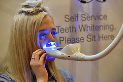 © Licensed to London News Pictures. 28/03/2016. A female visitor receives beauty treatment on her teeth at The Professional Beauty Show. The show is the largest in the UK and one of the largest in Europe. London, UK. Photo credit: Ray Tang/LNP