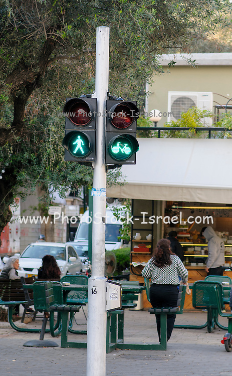 green Pedestrian and bicycle traffic light. As bicycle riding is becoming more popular special bicycle lanes are being built. Right of way is being managed with special lights for bicycles, pedestrians and cars. Photographed in Tel Aviv, Israel
