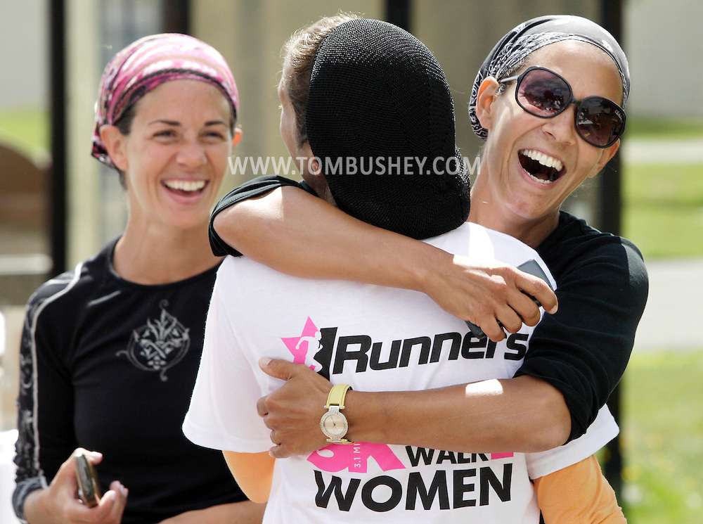 Suri Klein, right, congratulates Dasi Gobioff after Gobifoff finished the Jrunners 5K Run Walk for Women at Sullivan County Community College in Loch Sheldrake on Wednesday, July 27, 2011.  Michelle Aryeh is at left.  Many competitors in the race were Orthodox Jewish residents living at summer homes or bungalows in Sullivan County.