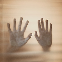 Hands being pressed against a window, suggesting a person trapped inside a room