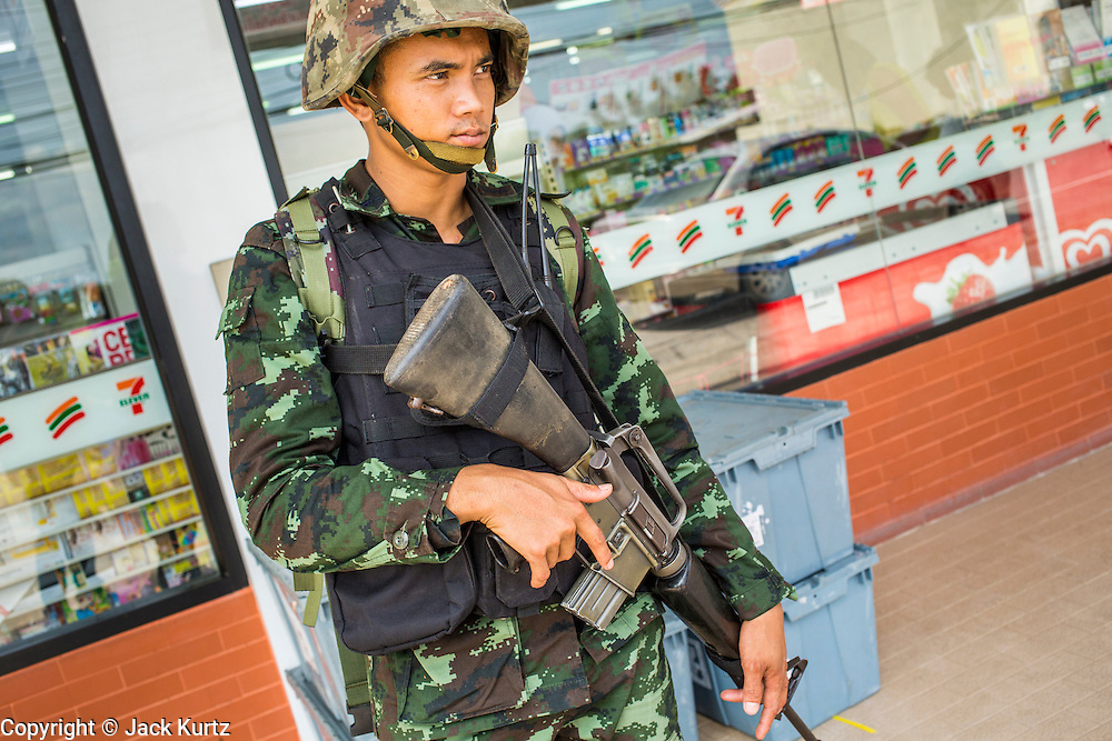 "25 OCTOBER 2012 - TAK BAI, NARATHIWAT, THAILAND: A soldier in the Royal Thai Army on duty in front of a 7-11 convenience store in Tak Bai, Thailand. The ""Tak Bai Incident"" took place on Oct. 25 in Tak Bai, Narathiwat, Thailand during the Muslim insurgency in southern Thailand. On that day, a crowd gathered to protest the arrest of local residents. Police made hundreds of arrests during the protest and transported the arrested to Pattani, about two hours away, in another province. They were transported in locked trucks and more than 80 people suffocated en route. This enraged local Muslims and shocked people across Thailand. No one in the Thai army accepted responsibility for the deaths and no one was ever charged. In the past, the anniversary of the incident was marked by protests and bombings. This year it was quiet. More than 5,000 people have been killed and over 9,000 hurt in more than 11,000 incidents, or about 3.5 a day, in Thailand's three southernmost provinces and four districts of Songkhla since the insurgent violence erupted in January 2004, according to Deep South Watch, an independent research organization that monitors violence in Thailand's deep south region that borders Malaysia.   PHOTO BY JACK KURTZ"