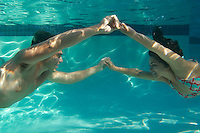 Young couple holding hands in swimming pool underwater