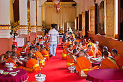 24 JUNE 2011 - CHIANG MAI, THAILAND: Monks at lunch at Wat Phra Singh in Chiang Mai, Thailand. Wat Phra Singh is the most revered Buddhist temple in Chiang Mai because it houses the Phra Singh (Lion Buddha). The exact origin of the Buddha is unknown though it is known to have resided in Buddhist temples in Sukothai, Ayuthaya, Chiang Rai and Luang Prabang before coming to Chiang Mai in approximately 1360.  PHOTO BY JACK KURTZ