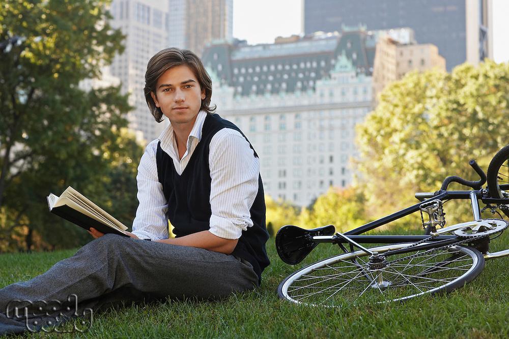 Man sitting on lawn holding book portrait