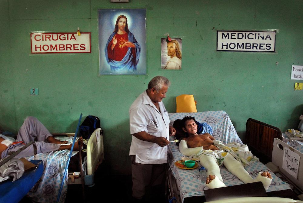 """Medardo Romero, auxiliar de mantenimiento, deja su escoba de lado para dar de comer a Miguel Zepeda, paciente manco y cuyo único brazo está enyesado. Estas dos áreas, """"cirugía hombres"""" y """"medicina hombres"""" deberían estar separadas, pues los recién salidos del quirófano requieren el ambiente más pulcro posible para recuperarse. Foto Mauro Arias"""