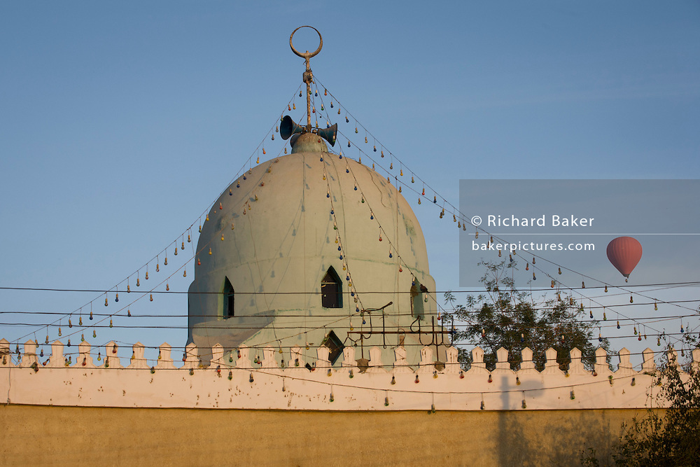A hot air balloon and the roof of a local mosque in a West Bank village of the modern city of Luxor, Nile Valley, Egypt.