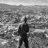Madagascar, Ambositra, Young man in hooded sweatshirt stands on hilltop overlooking city