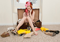 Portrait of young woman sitting in suitcase with footwear scattered on floor.