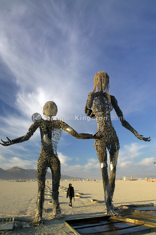"BLACK ROCK CITY, NV:  A Burning Man participant looks at a sculpture titled ""Passage"" by Dan Das Mann and Karen Cusolito in Black Rock City, Nevada."