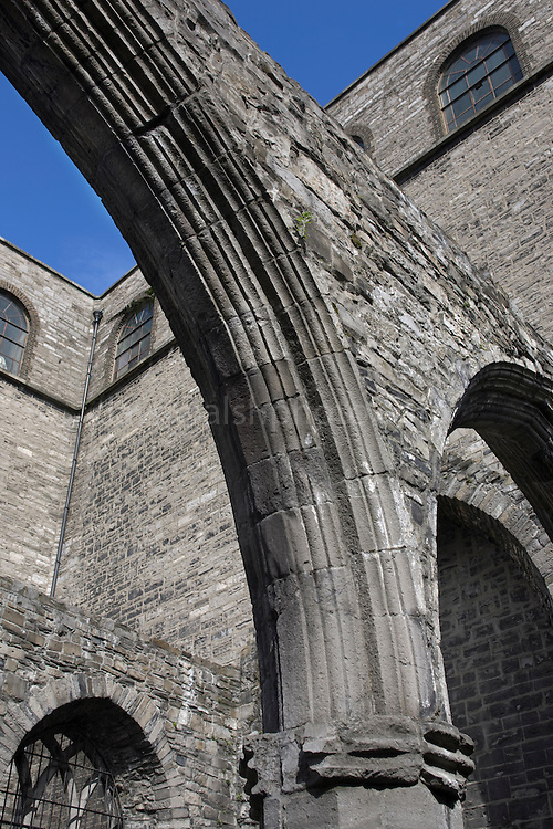 Exposed gothic arches in a disused section of St. Audeon's Church, in Dublin with the modern Catholic church behind. ....One of the oldest existing churches in Dublin, St. Audoens is a Norman church to St Ouen, built in 1190 to replace an earlier church to St Colmcille. The three bells in the belltower are reported to date to 1423. The mysterious Lucky Stone, an early Christian grave marker, is in the porch, where it has been since 1309. The main porch also houses the Portleister Tomb, featuring two carved effigys of the church benefactor and his wife. ..