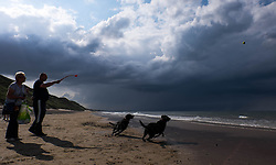 © Licensed to London News Pictures.05/07/15<br /> Saltburn by the Sea, UK. <br /> <br /> A couple play with their dogs as storm clouds pass over the north sea off the coastline at Saltburn by the Sea. <br /> <br /> Photo credit : Ian Forsyth/LNP