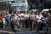 People are driving motorcycles in heavy traffic on a street in Saigon (Ho Chi Minh City) Vietnam.