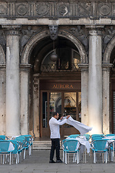 A waiter prepares tables at a cafe in St Mark's Square in Venice. From a series of travel photos in Italy. Photo date: Tuesday, February 12, 2019. Photo credit should read: Richard Gray/EMPICS