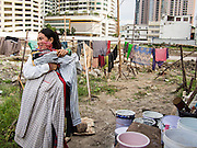 05 SEPTEMBER 2013 - BANGKOK, THAILAND:  A Cambodian woman brings in her dry laundry after her shift on the construction site of a new high rise apartment / condominium building on Soi 22 Sukhumvit Rd in Bangkok. Other residential high rise buildings ring the site. The workers live in the corrugated metal dorms on the site. Most of the workers at the site are Cambodian immigrants.             PHOTO BY JACK KURTZ