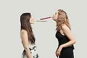 Two young women blowing party puffers while looking at each other against gray background