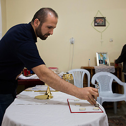 Father Adday, 34, prepares for mass at an apartment in Kirsehir, Turkey. <br /> Father Adday celebrated a mass in this apartment with about 30 people. There are no Catholic churches in this part of the country and when Father Adday visits the Eucharist is celebrated in homes.