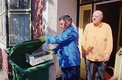 Male carer assisting client by putting rubbish into wheelie bin,