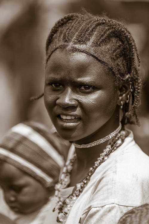 Portrait of a young Fulani mother in a local market in northern Burkina Faso. The Fulani or Peul are nomadic herdsmen of the Sahel region of West Africa. The darker lower lip from indigo staining, facial tattoos and silver jewellery are traditional markings of Fulani women.