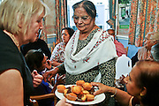Local residents enjoy ftea and cakes during a multi faith party at the Neighbourly Care day centre in Southall.