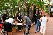 Baltimore, Maryland - June 20, 2018: Baltimore City Health Department fellows, Olivia Carvajal, behind the table, and Leah Hill, right, offer training on how to use the nasal spray opioid overdose reversal drug Naloxone (brand name Narcan) outside Baltimore's famed Lexington Market June 20, 2018. After three minutes of instruction, trainees receive one kit, which the city bought at half-price for $75, for free. <br /> <br /> <br /> <br /> CREDIT: Matt Roth for The New York Times<br /> Assignment ID: 30221297A
