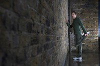 Young man doing leg stretch against brick wall