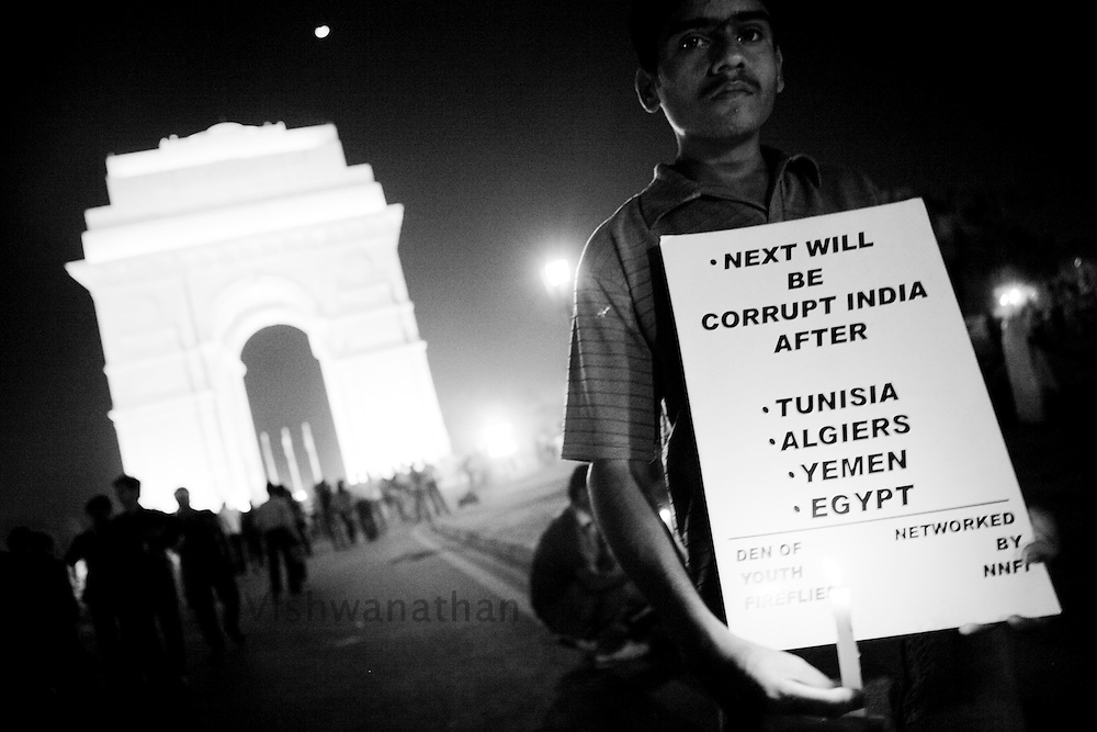 A supporter of social activist Anna Hazare holds up a sign referencing protests in the Middle East during a candlelight vigil in New Delhi, India, on Thursday, April 7, 2011. Hazare has vowed to fast to the death to rid India of the corruption he says is its biggest curse. Photographer: Prashanth Vishwanathan
