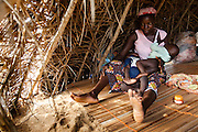 Amelie Adoko, 42, two of a friend's children while sitting in a basic shelter made of palm leaves near the village of Kpoto, Benin on Wednesday October 27, 2010. Most of the village was destroyed by floods that have hit the country over the past few weeks, forcing its 1500 to flee. They now live in a makeshift camp located about 500 meters from the village. Amelie looks after a friend's children while she's gone to the market.