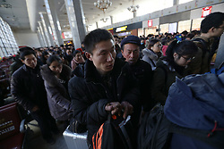 epa05830818 Chinese migrant worker Wang Pengfei (C) queues with hordes of travelers at the Beijing Railway station on his journey back to his hometown for the Spring Festival in Beijing, China, 22 January 2017. Wang is the migrant worker and is working in the capital city as a delivery man. He will travel to visit his family in the Shandong Province for the annual Chinese Lunar New Year or Spring Festival. This is the only time he gets to see his family each year. Wang will join millions of fellow Chinese travelers making their way back home as they pack trains, planes and buses, in what is the largest human migration in the world. The journey, known as 'Chunyun' - the annual spring migration, will involve a total of 2,98 billion trips, starting from 13 January and continuing until 21 February 2017.  EPA/HOW HWEE YOUNG