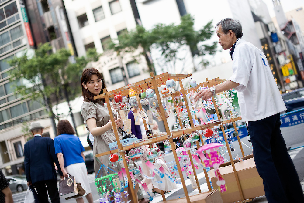 A woman looks at Edo furin, or glass wind chime hanging from a portable wooden frame in the chic Ginza district in Tokyo, Japan. The chimes, which date back more than 200 years in Japan, were traditionally carried around town dangling from  bamboo poles by sellers. Sasaki is one of a few people who continue this trend.A customer admires Edo furin, or glass wind chimes, displayed on a wooden frame by seller Yoshitomo Sasaki in the chic Ginza district in Tokyo, Japan. The chimes, which date back more than 300 years in Japan, were traditionally carried around town dangling from  bamboo poles by sellers. Sasaki is one of a few people who continue this trend.