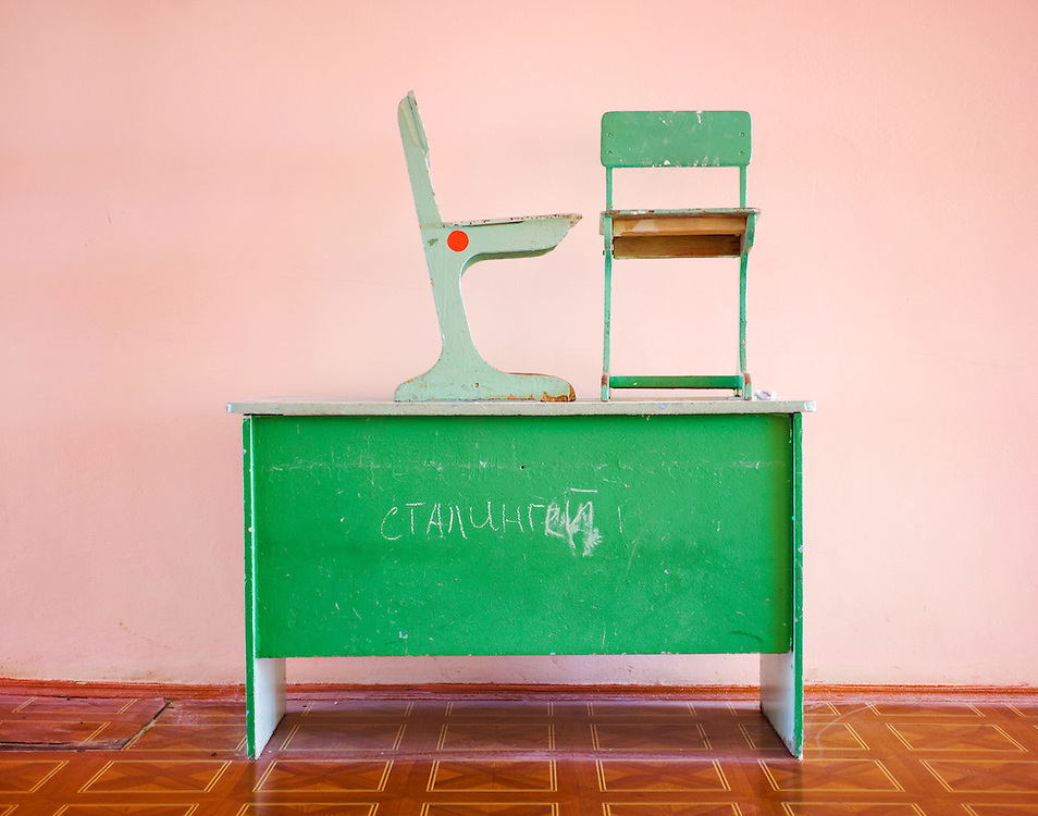 <b>Photograph by Frank Ward:</b><br>A desk with graffiti sits in a corridor of a high school in Kalmykia.