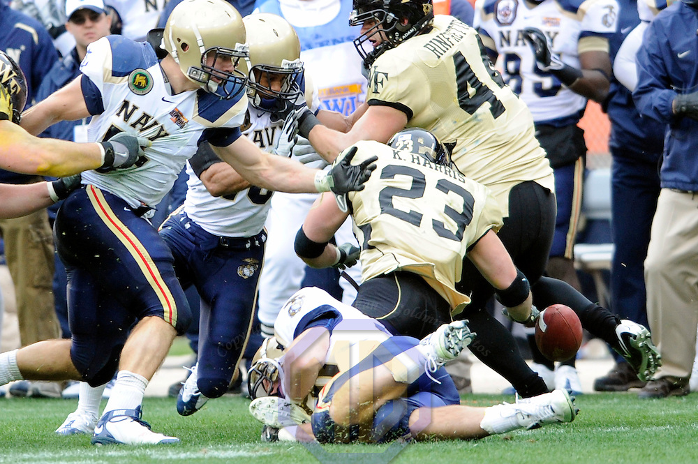 20 December 2008:   Wake Forest running back Kevin Harris (23) fumbles the ball out of bounds after a 5-yard gain in the 2nd quarter after a tackle by Navy safety Jarrod Shannon (10).  The Wake Forest University Demon Deacons defeated the Naval Academy Midshipmen 29-19 in the inaugural EagleBank Bowl in Washington, D.C.