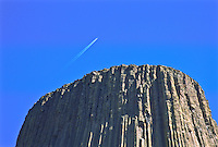 A jet flying over Devils Tower National Monument creating a contrail.  Wyoming.