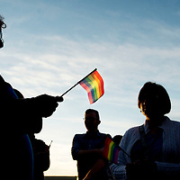 """The setting sun illuminates a gay pride flag held by Dina Doerfer of Millcreek Township, Pa., as she attends a vigil held Sunday, June 12, 2016, at Erie, Pa.'s Zone Dance Club to remember the victims of the mass shooting that occurred in Orlando, Fla.'s Pulse night club early that morning. Between 75 and 100 people attended the Erie event, according to organizers from NWPA Pride, an Erie region LGBT organization. """"These people are my family,"""" said Doerfer, who said she is a lesbian, as she looked around the crowd. """"To consider the fact that that could've been us down there (in the Orlando club), that's very disturbing. Love is love and we need to be able to (gather) regardless."""" Vigil organizers said the gathering was a way for members and allies of Erie's LGBTQ community to stand in solidarity with those affected by the shooting at Pulse, itself a gathering place for Orlando's gay community. Photo by Andy Colwell, Erie Times-News"""