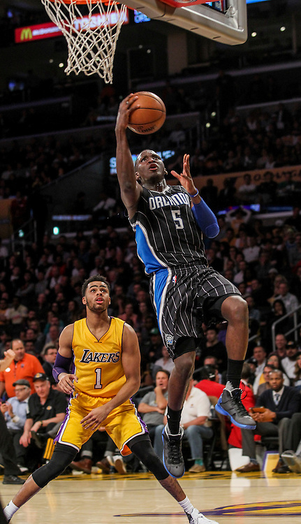 Los Angeles Lakers guard D'Angelo Russell, left, looks on as Orlando Magic guard Victor Oladipo goes up for a lay up during the first half of an NBA basketball game Tuesday, March 8, 2016, in Los Angeles.  (AP Photo/Ringo H.W. Chiu)