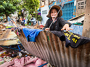 16 NOVEMBER 2015 - BANGKOK, THAILAND:  A woman hangs her laundry out to dry in the Wat Kalayanamit neighborhood. She's using a temporary fence in front of a demolished home to hang her laundry. Fifty-four homes around Wat Kalayanamit, a historic Buddhist temple on the Chao Phraya River in the Thonburi section of Bangkok, are being razed and the residents evicted to make way for new development at the temple. The abbot of the temple said he was evicting the residents, who have lived on the temple grounds for generations, because their homes are unsafe and because he wants to improve the temple grounds. The evictions are a part of a Bangkok trend, especially along the Chao Phraya River and BTS light rail lines. Low income people are being evicted from their long time homes to make way for urban renewal.          PHOTO BY JACK KURTZ