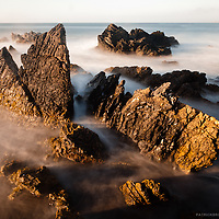Using a ND filter enabling a long exposure on the jagged rocks of Punta de Lobos during the golden, misting the turbulent ocean against the golden rocks.