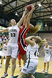 29 January 2011: Olivia Lett gets a hand on a shot by Kristi Schmidt  during an NCAA Womens basketball game between the Carthage Reds and the Illinois Wesleyan Titans at Shirk Center in Bloomington Illinois.