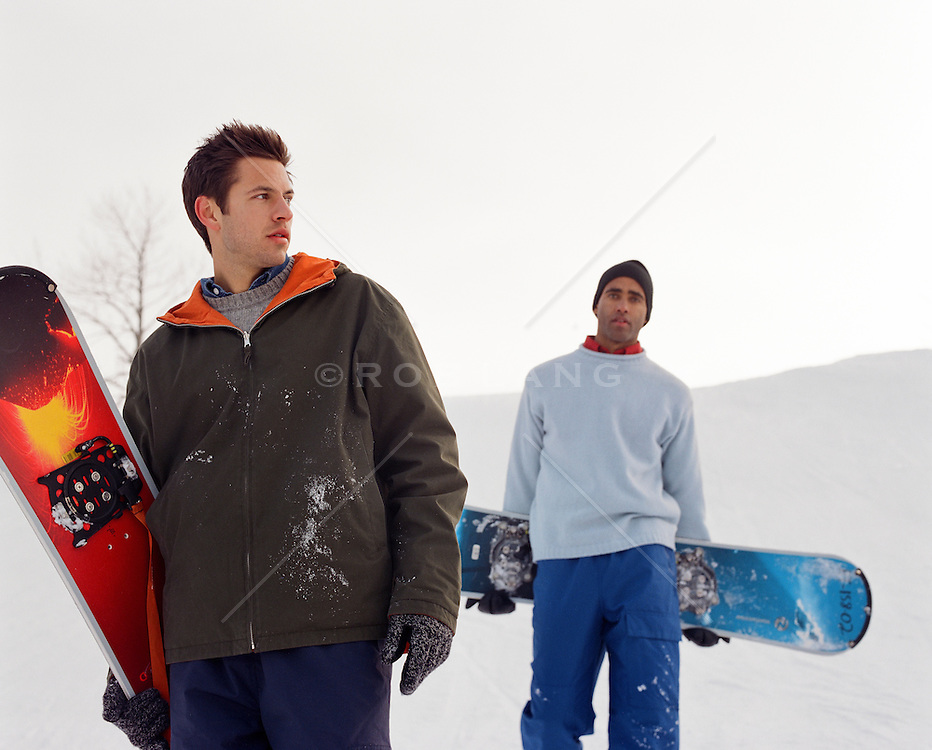 two men with snowboards on a mountain