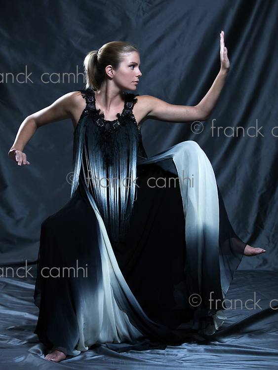 fashion pictures of a beautiful woman wearing silk fringe black and white dress chinese style doing martial arts posture
