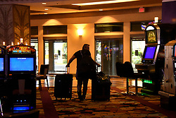March 17, 2020, Las Vegas, Nevada, USA: A last minute guest makes his way out of New York New York hotel and casino totally as it is being closed down due to Coronavirus.  (Credit Image: © Gene Blevins/ZUMA Wire)
