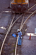 A Union Pacific employee applies a 'blue flag' to a track in the giant Proviso Freight Yard in suburban Chicago. The flag is to protect employees who may be working on equipment on that track.