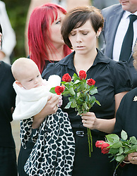 © licensed to London News Pictures. 08/09/2011. Brize Norton, UK. Joanne Weston (right) wife of Sergeant Barry Weston holding her daughter Roseas the coffin of Sergeant Barry Weston of 42 Commando Royal Marines passes through the town of Carterton, Oxfordshire today (08/09/2011). Today was the first time a repatriation had passed through RAF Brize Norton. Sgt Weston was killed on August 30 while leading a patrol near the village of Sukmanda in southern Nahr-e Saraj, Helmand province. Photo credit: Ben Cawthra/LNP
