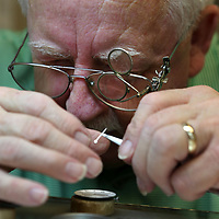 Keeping a sharp eye on his work, Scott uses tweezers to put the hands back on a watch brought in by a customer.