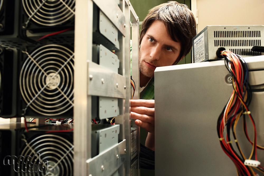 Young man fixing computer equipment.