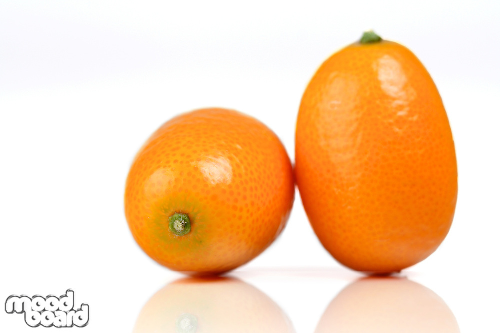 Close-up of kumquats on white background