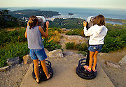 Two young girls look through binoculars at Penobscot Bay from the Camden Overlook in Camden, Maine, USA.