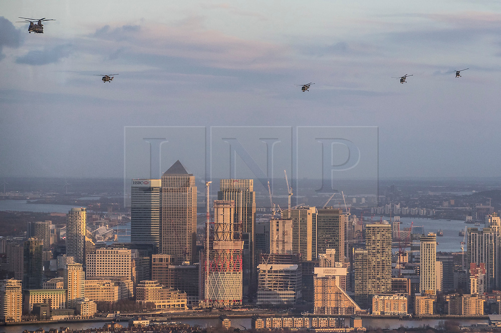 © Licensed to London News Pictures. 16/01/2018. London, UK.  The last four remaining British Army Lynx helicopters are escorted by a Chinook as they fly in formation over Canary Wharf in London. The British made aircraft is being decommissioned after almost 40 years in service. Photo credit: Peter Macdiarmid/LNP