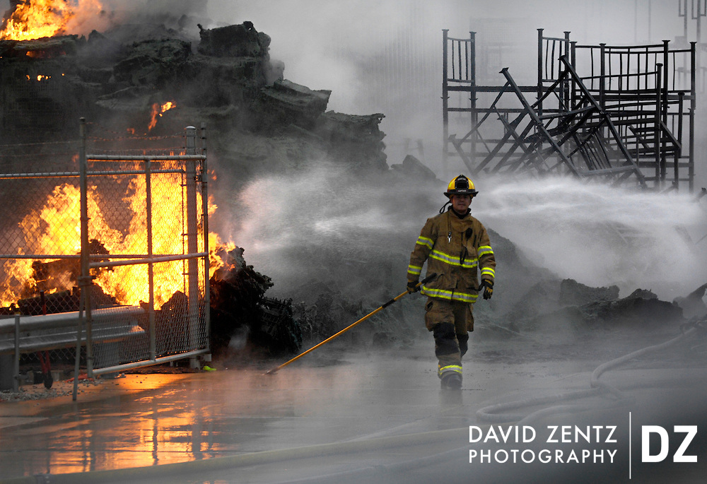A firefighter walks away from a burning pile of plastic pallets at a multiple alarm fire at the Morton Welding building in Morton, Ill.
