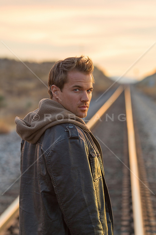 good looking man looking back over his shoulder while on railroad tracks in New Mexico at sunset